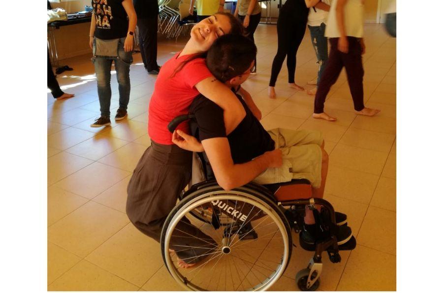 Una joven sin discapacidad y un joven con discapacidad se entrelazan en un baile