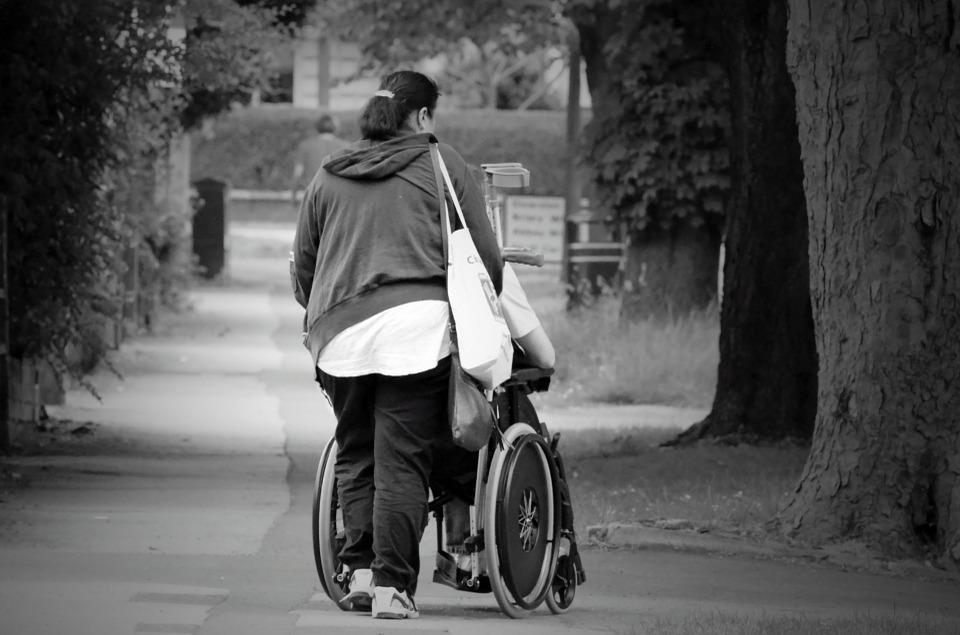 Foto de una mujer con una persona en silla de ruedas