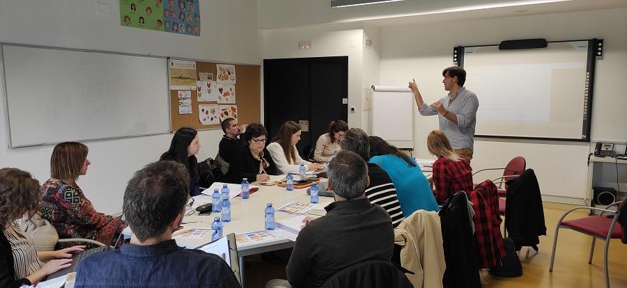 Fotografía de los asistentes a la reunión en una mesa atendiendo a una explicación del coordinador