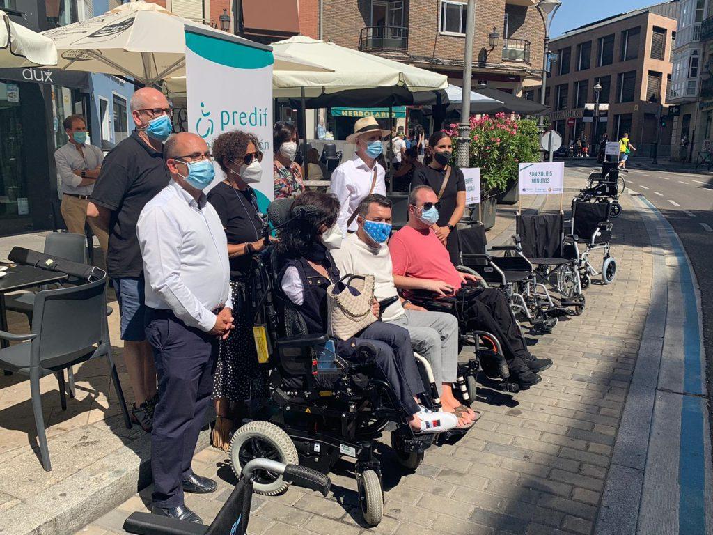 Miembros de ASPAYM, PREDIF y el Ayuntamiento de Valladolid posan para los medios en aparcamientos ocupados por sillas de ruedas
