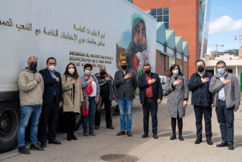 Miembros de diferentes entidades colaboradoras posan llevándose la mano al corazón
